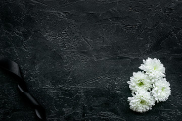 Funeral symbols. White flower near black ribbon on black background top view copy space Wall mural