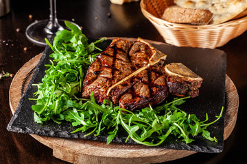 The concept of Italian cuisine. Juicy T-bone steak of beef aging stewed meat, with rucola salad and cherry tomatoes. A glass of red wine and bread basket on the table