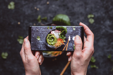 Photographing food. Hands taking picture of delicious vegetable salad with smartphone.