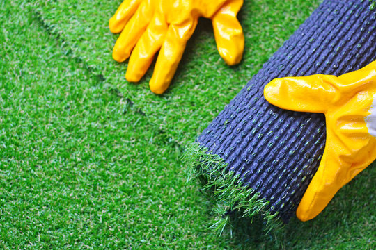 Hand of a worker with a artificial lawn grass. Artificial turf laying background.