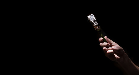 male hand holding a brush with white paint on a black background. Man in industrial concept.