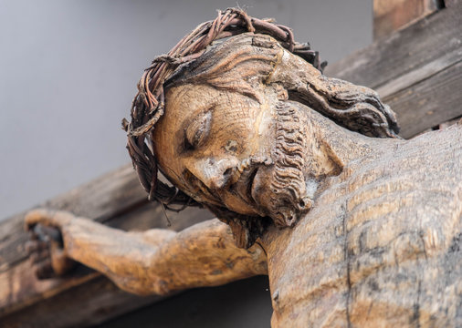 Holy Crucified Jesus Christ close-up. Ancient wooden sculpture. Bottom view. Sacred figure.
