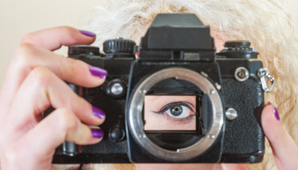 Womans eye looking through the open mirror box of a vintage 35mm film SLR camera