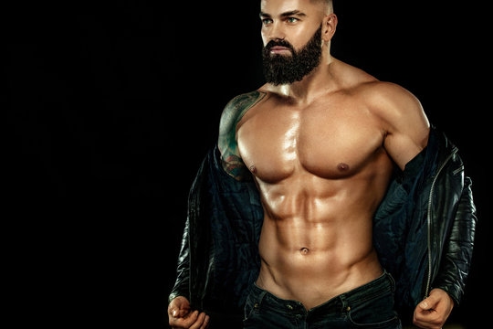 Men fashion concept. Close-up portrait of a brutal bearded man topless in a leather jacket. Athlete bodybuilder on black background.