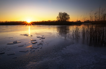 Winter landscape with frozen river, reeds and sunset sky. Daybreak