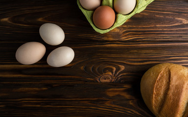 Eggs and bread on wooden table Top view