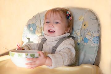 little girl is eating porridge