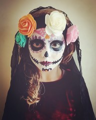Portrait of a girl with ceremonial sugar skull make-up for Halloween
