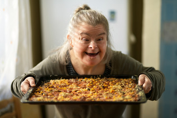 portrait of adult woman with down syndrome holding pizza