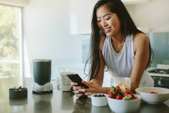 Woman social networking in morning on mobile phone