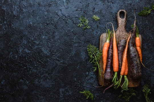 Fresh harvested organic carrots on wooden cutting board on black background top view