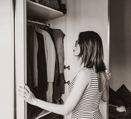 Young girl choosing a clothes in wardrobe. . Image in black and white color style
