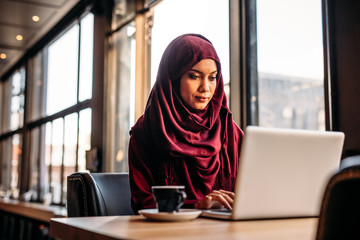 Businesswoman in hijab working from a coffee shop