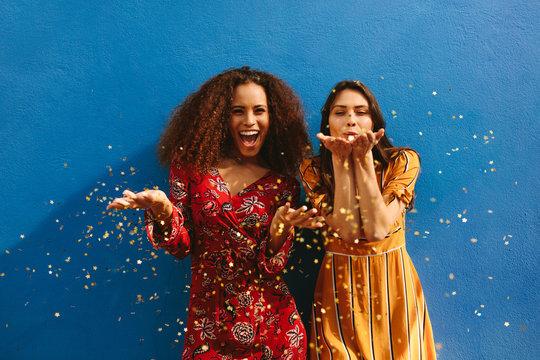Female friends blowing off magic glitter