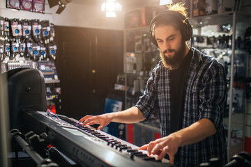 Serious and concentrated young man playing on keyboard. He listen to music through headphones. It is sunny inside.