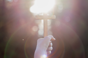 human hands praying to the GOD while holding a crucifix symbol with bright sunbeam on the sky
