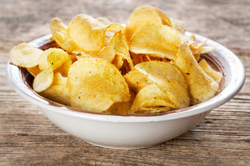 potato chips in bowl on wooden background
