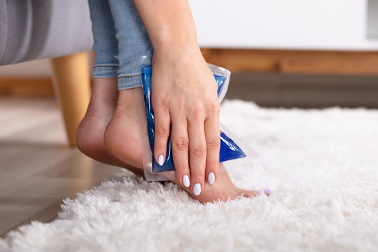 Woman Applying Ice Gel Pack On Her Ankle