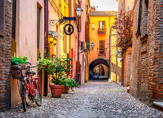 Fototapeta Cozy narrow street in Ferrara, Emilia-Romagna, Italy. Ferrara is capital of the Province of Ferrara