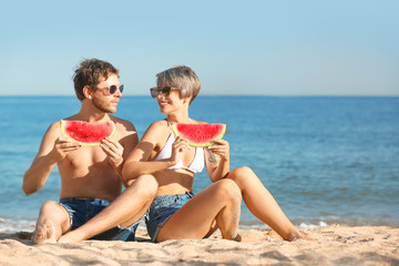 Young couple with watermelon slices on beach