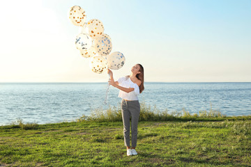 Beautiful teenage girl holding glitter balloons on riverside