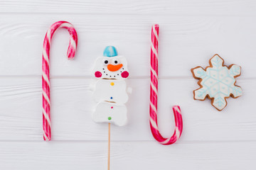 Christmas sweets background. Candy canes, candy snowman and gingerbread snowflake. Winter holidays treats.