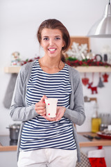 Portrait of young woman against kitchen interior background