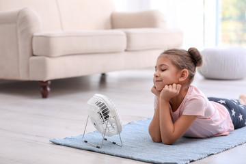 Little girl relaxing in front of fan at home. Summer heat