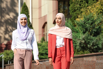 Muslim women in hijabs outdoors on sunny day