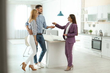 Female real estate agent giving house key to couple indoors