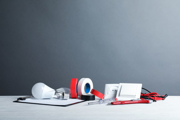 Set of electrician's tools on table against gray background. Space for text