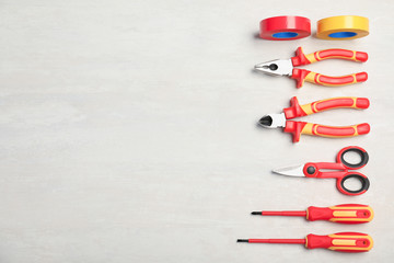 Flat lay composition with electrician's tools and space for text on light background