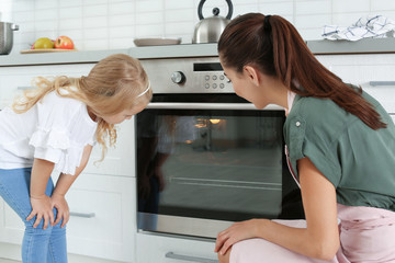 Young woman and her daughter baking something in oven at home