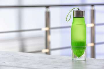 Sports water bottle on table against blurred background. Space for text