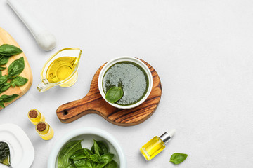 Composition with basil oil and leaves on white table. Space for text