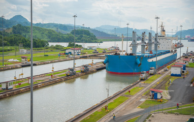 Poster Kanaal Large cargo ships pass through the Panama Canal locks. This everyday event, provides income from both fees, and tourism, for the whole country.
