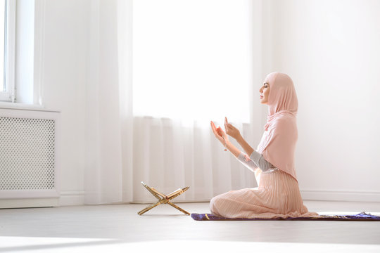 Muslim woman in hijab praying on mat indoors