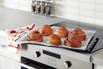 Tray with freshly oven baked buns on stove in kitchen