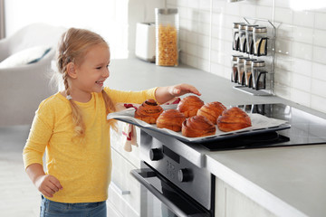 Little girl with tray of oven baked buns in kitchen