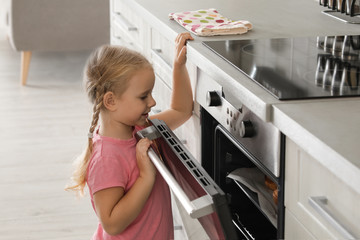 Little girl opening oven while baking in kitchen