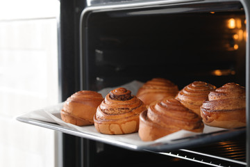 Open oven with tray of freshly baked buns, closeup