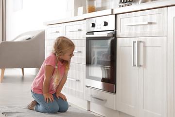 Little girl sitting near oven in kitchen