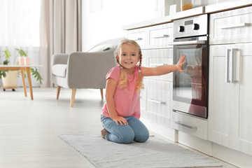 Little girl sitting near oven in kitchen. Space for text