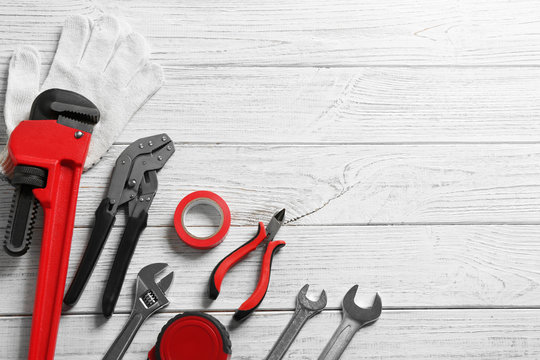 Flat lay composition with plumber's tools and space for text on wooden background