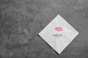 Paper napkin with lipstick mark and words CALL ME on grey background, top view. Space for text