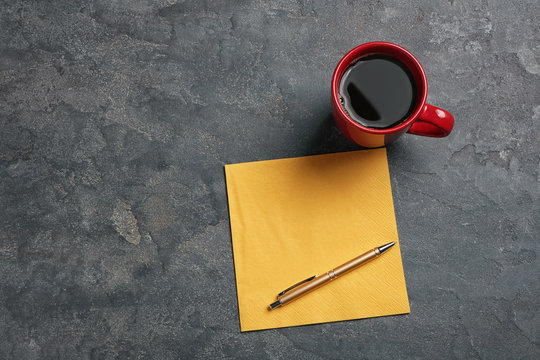 Clean napkin, cup of coffee and pen on grey background, top view with space for text