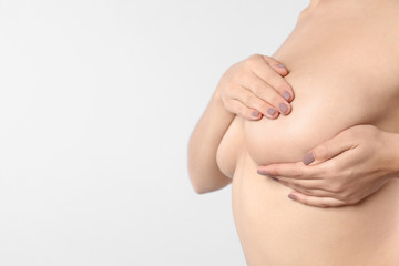 Woman checking her breast and space for text on white background, closeup