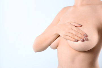 Woman covering her breast and space for text on white background, closeup. Self examination