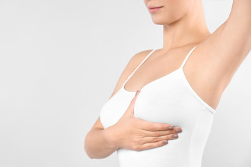 Woman checking her breast on white background, closeup. Space for text