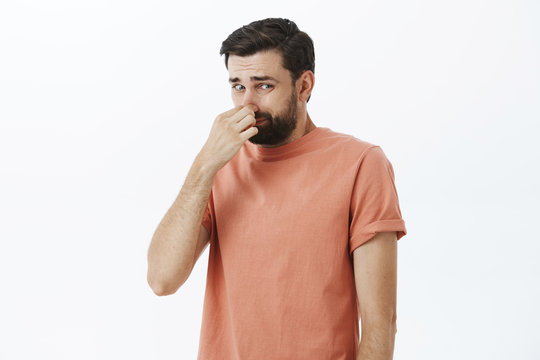 Gosh it stinks. Disgusted and displeased unhappy male with beard closing nose with fingers looking at creepy and awful object which reeks with terrible smell looking at lower right corner dissatisfied